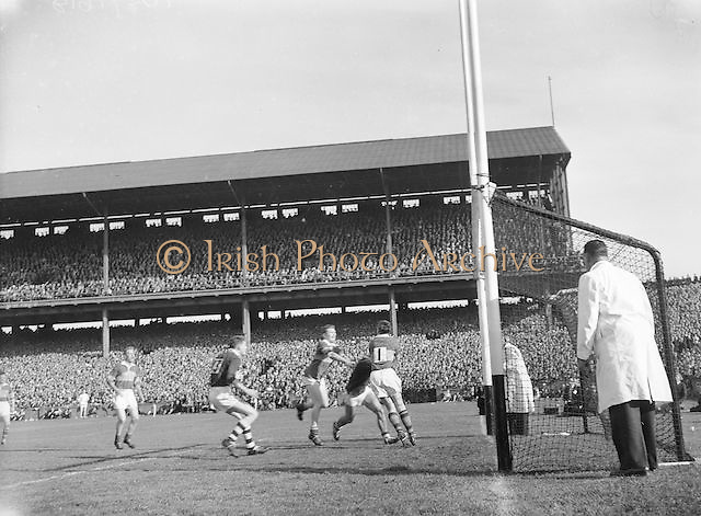 Kerry Goalie J Culloty gathers the ball safely despite the efforts of Galway J Young S Keeley during the All Ireland Senior Gaelic Football Championship Final, Kerry vs Galway in Croke Park on the 27th September 1959. Kerry 3-7 Galway 1-4. Alied Irish Bank Ansley Bridge Poplar Rd, Fairview North Srand, East Wall Rd Houses, Shiriff St Church Clouds Howth Cornmarket, St Brendans March 1987
