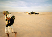 A camel trader walks away from camp in the Saharah desert in the south of Tunisia