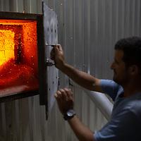 Moises Madrid closes the furnace door on the coffee dryer at La Laguna.