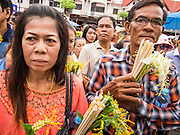 """22 JULY 2013 - PHRA PHUTTHABAT, THAILAND: People wait to present flowers to monks during the Tak Bat Dok Mai at Wat Phra Phutthabat in Saraburi province of Thailand, Monday, July 22. Wat Phra Phutthabat is famous for the way it marks the beginning of Vassa, the three-month annual retreat observed by Theravada monks and nuns. The temple is highly revered in Thailand because it houses a footstep of the Buddha. On the first day of Vassa (or Buddhist Lent) people come to the temple to """"make merit"""" and present the monks there with dancing lady ginger flowers, which only bloom in the weeks leading up Vassa. They also present monks with candles and wash their feet. During Vassa, monks and nuns remain inside monasteries and temple grounds, devoting their time to intensive meditation and study. Laypeople support the monastic sangha by bringing food, candles and other offerings to temples. Laypeople also often observe Vassa by giving up something, such as smoking or eating meat. For this reason, westerners sometimes call Vassa the """"Buddhist Lent.""""     PHOTO BY JACK KURTZ"""