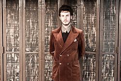 Man Wearing Velvet Jacket Standing in front of Shutters