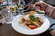 A fancy rösti or röschti dinner plate is heaped with potatoes, egg, bacon, tomato and pickles at Hotel Oberland, Lauterbrunnen village, in the canton of Bern, Switzerland, the Alps, Europe.