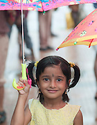 Young girl sheltering from monsoon rains, Cochin, Kerala, India.