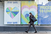 22nd February, Cheltenham, England. A woman walks past Primark, which is shut under the ongoing national lockdown restrictions.