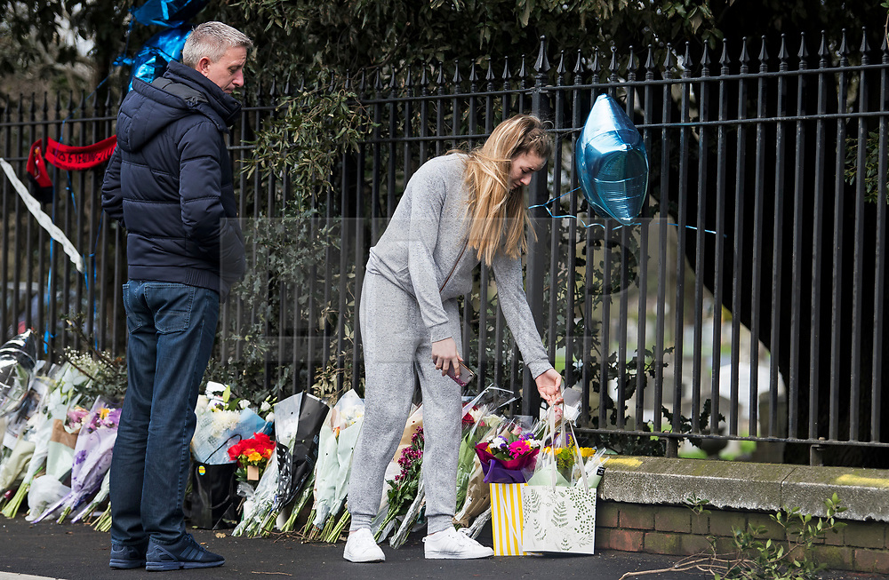 © Licensed to London News Pictures. 28/01/2018. London, UK. An emotional young woman aged 16 places flowers at the scene where three teenage pedestrians were killed near a bus stop in Hayes, West London when a black Audi collided with them. Named locally as Harry Rice, Josh Kennedy and George Wilkinson, the three teenagers were hit on Friday night  close to the M4 Junction 4. A 28-year-old man has been arrested and a police are currently looking for a  second man believed to have been in the Audi.. Photo credit: Ben Cawthra/LNP