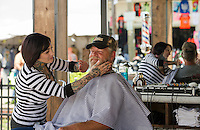 """Heather Manto of Shed Barber Shop in Austin TX gives Clay """"Mudd"""" Carroll a beard trim and shave at Flo's Chop Shop on Lakeside Avenue at the Progressive Insurance booth.  (Karen Bobotas/for the Laconia Daily Sun)"""