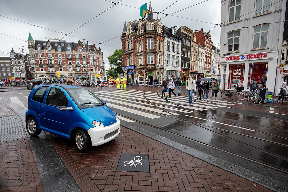Op het Muntplein in Amsterdam rijdt een brommobiel het fietspad op.<br /> <br /> A microcar takes a turn to the bicycle lane at the Munt Square in Amsterdam.