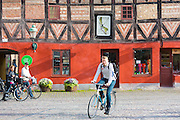 Young man cycling in old town square in Malmo, Sweden