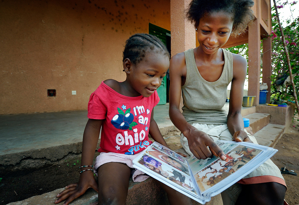 Three-year old Naomi Wallet Tafaki and her 21-year old sister Monique Kone look at an album of family photographs in a Catholic training center in Niamana, Mali. Several families displaced by the fighting in northern Mali took refuge in the center.