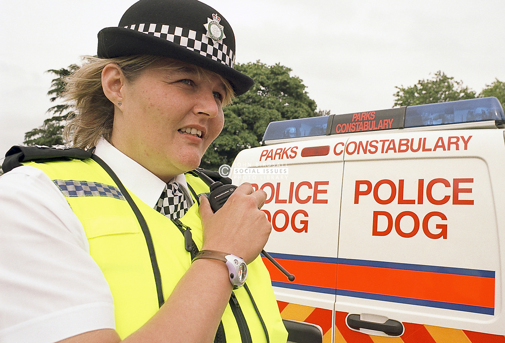 Parks Constabulary Policewoman by Police Dog van on radio in Finsbury Park Haringey London UK