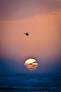 The sun sets at Kaena Point of Oahu with a helicopter flying in the air above the sun.