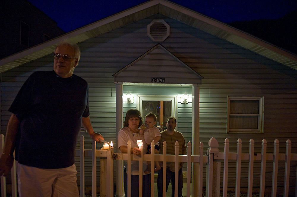 John Bell, left, Marshelle Pettry, Jaxson Pettry, 12 months and Tim Pettry chat after a candlelight vigil in Whitesville, WV on Wednesday, April 7, 2010.  Communities across Boone and Raleigh counties held vigils and services for the fallen miners and their families.