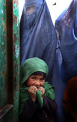 KABUL,AFGHANISTAN - SEPT. 10:  An Afghan child waits with her mother to buy bread at a subsidized price from a bakery run by widowed women set up to help vulnerable families in Kabul, Afghanistan September 10,2002. (Photo by Ami Vitale/Getty Images)