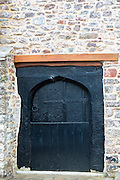 Typical traditional wooden cottage door on old stone building at Porlock in Somerset, United Kingdom