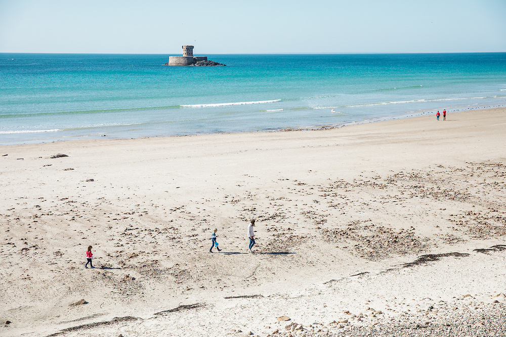 Mum and children walking, collecting shells on St Ouen's Bay, Jersey with views of La Rocco Tower surrounded by turquoise clear water beyond