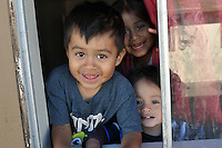 Children play in an apartment window at 1337 Garner Ave in east Salinas. Saturday's intense fire ravaged part of the complex, leaving many families homeless.