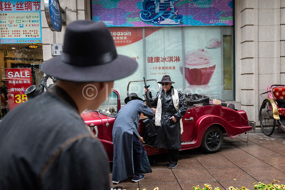 A tourist dressed as a 1920s Shanghai gangster poses for a photograph near the Nanjing Road shopping district in in Shanghai, China, on Sunday, July 3, 2016.