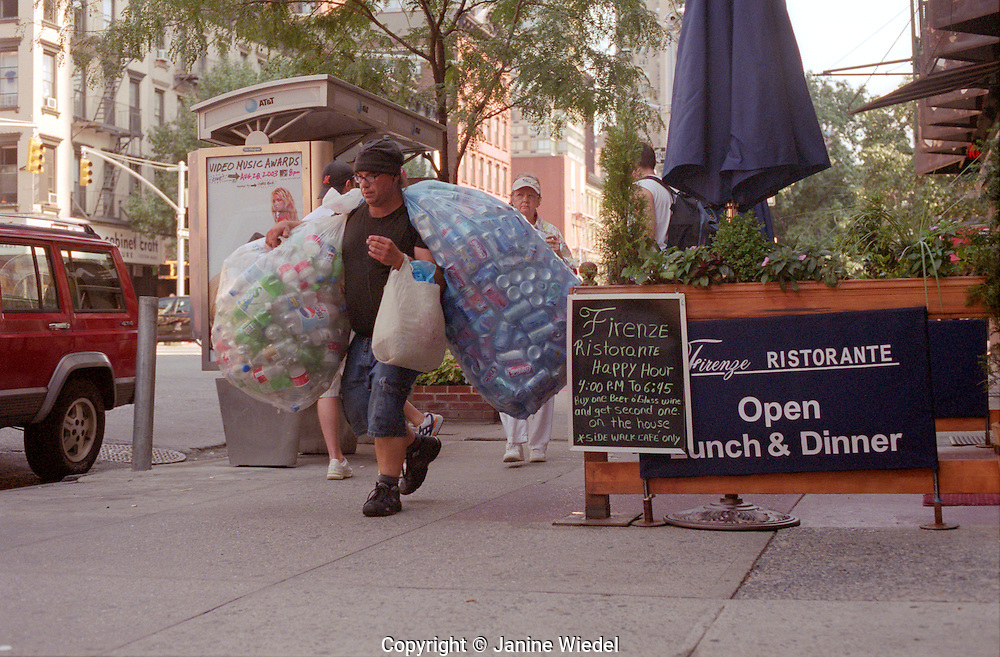 Homeless person collecting tin cans  in New York City.