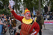 Jester protester with a long fake nose shouts about her 'dirty money' at Extinction Rebellion demonstration on 3rd September 2020 in London, United Kingdom. With government resitting after summer recess, the climate action group has organised two weeks of events, protest and disruption across the capital. Extinction Rebellion is a climate change group started in 2018 and has gained a huge following of people committed to peaceful protests. These protests are highlighting that the government is not doing enough to avoid catastrophic climate change and to demand the government take radical action to save the planet.