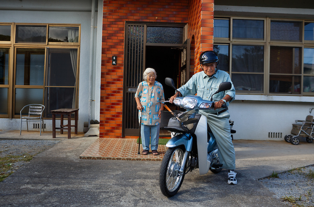 Fumi Tamaki escorts her husband, farmer Shimpuku Tamaki, 98, as he leaves home on his motorbike to check on his crops.