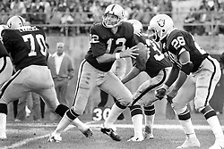"""Oakland Raider QB Kenny """"The Snake"""" Stabler drops back to pass. Protection by Henry Lawarence #70 and Clarence Davis #28. (1977 photo by Ron Riesterer)"""