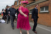 Large lady in pink arrives with family or friends during the annual Royal Ascot horseracing festival in Berkshire, England. Royal Ascot is one of Europe's most famous race meetings, and dates back to 1711. Queen Elizabeth and various members of the British Royal Family attend. Held every June, it's one of the main dates on the English sporting calendar and summer social season. Over 300,000 people make the annual visit to Berkshire during Royal Ascot week, making this Europe's best-attended race meeting with over £3m prize money to be won.