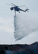 A fire fighting helicopter drops water on a brushfire, Sunday, Sept. 3, 2017, in Burbank, Calif. Several hundred firefighters worked to contain a blaze that chewed through brush-covered mountains, prompting evacuation orders for homes in Los Angeles, Burbank and Glendale.(Photo by Ringo Chiu)<br /> <br /> Usage Notes: This content is intended for editorial use only. For other uses, additional clearances may be required.