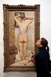 Visitor looking at painting Standing Nude by George Hendrik Breitner at Royal Museum for Fine Arts in Antwerp Belgium