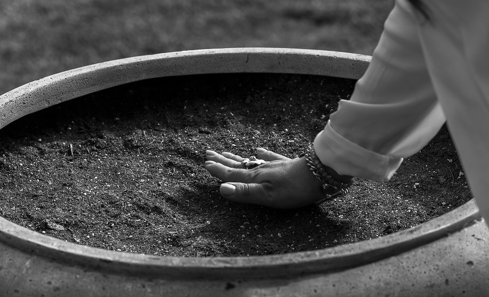 A family member pats the dirt in one of three pots where Nikko's ashes were planted during the memorial.