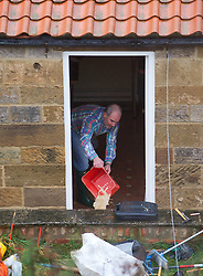© Licensed to London News Pictures. 25/11/2012..North East England..The owner of a house on the outskirts of Saltburn fights to bail out flood water following a night of heavy rain that caused traffic disruption and flooding in parts of Cleveland and North Yorkshire...Photo credit : Ian Forsyth/LNP