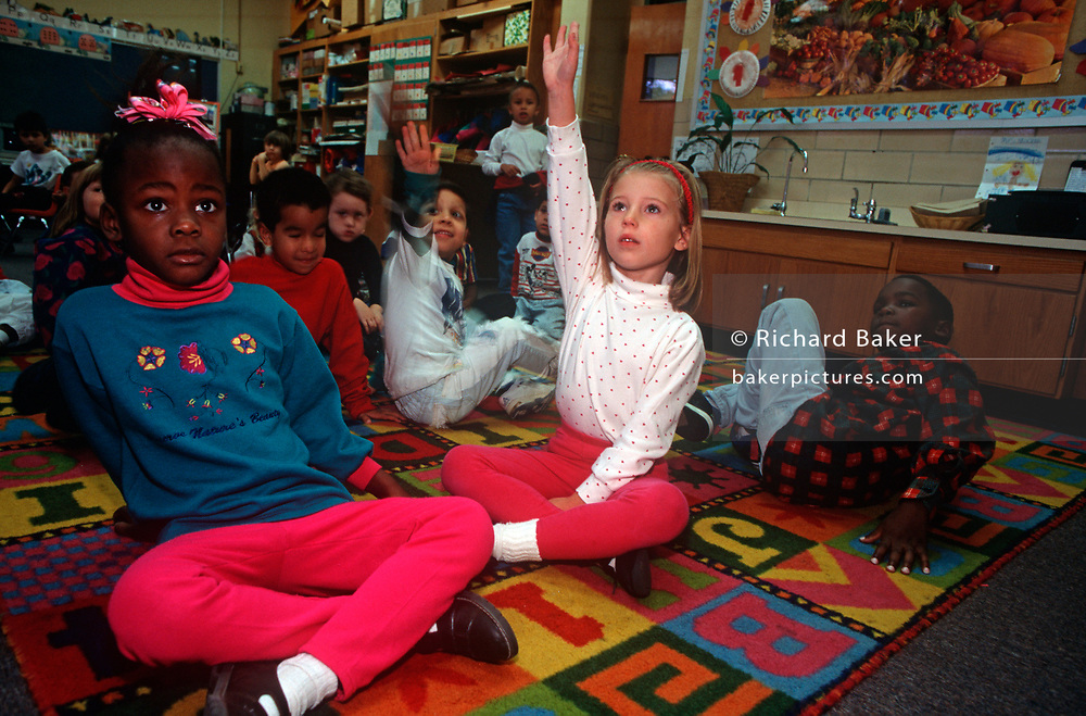 A confident 1990s child raises her hand while classmates sit on a classroom rug at the Ashford Park Elementary School, on 5th November 1995, in Atlanta, Georgia USA. (Photo by Richard Baker / In Pictures via Getty Images)