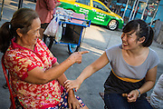 28 MARCH 2013 - BANGKOK, THAILAND:  Michelle Kao (right) talks to Noi, a woman who lives in her neighborhood.     PHOTO BY JACK KURTZ
