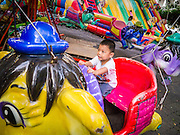 """27 NOVEMBER 2012 - BANGKOK, THAILAND:   A child on a ride on the midway at the Wat Saket Temple Fair in Bangkok. Wat Saket, popularly known as the Golden Mount or """"Phu Khao Thong,"""" is one of the most popular and oldest Buddhist temples in Bangkok. It dates to the Ayutthaya period (roughly 1350-1767 AD) and was renovated extensively when the Siamese fled Ayutthaya and established their new capitol in Bangkok. The temple holds an annual fair in November, the week of the full moon. It's one of the most popular temple fairs in Bangkok. The fair draws people from across Bangkok and spills out in the streets around the temple.   PHOTO BY JACK KURTZ"""