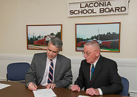 Steve Tucker signs the formal letter as Superintendent for Laconia schools with Mal Murray on Friday afternoon during the Laconia School Board meeting.  (Karen Bobotas/for the Laconia Daily Sun)