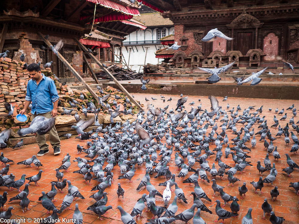30 JULY 2015 - KATHMANDU, NEPAL:    A man feeds pigeons amidst piles of ruble and bricks stacked for recycling in Durbar Square in Kathmandu. Three months after the earthquake most of the tourist attractions are open but signs of the tremblor remain. The Nepal Earthquake on April 25, 2015, (also known as the Gorkha earthquake) killed more than 9,000 people and injured more than 23,000. It had a magnitude of 7.8. The epicenter was east of the district of Lamjung, and its hypocenter was at a depth of approximately 15km (9.3mi). It was the worst natural disaster to strike Nepal since the 1934 Nepal–Bihar earthquake. The earthquake triggered an avalanche on Mount Everest, killing at least 19. The earthquake also set off an avalanche in the Langtang valley, where 250 people were reported missing. Hundreds of thousands of people were made homeless with entire villages flattened across many districts of the country. Centuries-old buildings were destroyed at UNESCO World Heritage sites in the Kathmandu Valley, including some at the Kathmandu Durbar Square, the Patan Durbar Squar, the Bhaktapur Durbar Square, the Changu Narayan Temple and the Swayambhunath Stupa. Geophysicists and other experts had warned for decades that Nepal was vulnerable to a deadly earthquake, particularly because of its geology, urbanization, and architecture.     PHOTO BY JACK KURTZ