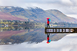 © Licensed to London News Pictures. 13/03/2018. Pooley Bridge UK. A man stands at the end of the pier at the Duke of Portland Boathouse in Pooley Bridge this morning adding a little colour to a mostly over cast day at Ullswater in Cumbria as the UK prepares for more freezing temperatures in the coming days. Photo credit: Andrew McCaren/LNP