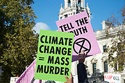 Demonstration in Parliament Square called by Extinction Rebellion to protest the government's inaction on climate change and calling for a mass rebellion and civil disobedience on 31st October 2018 in London, United Kingdom. Protesters hold placards saying Climate change equals mass murder and Tell the truth.
