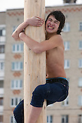 Istra, Russia, 06/03/2011..A young man climbs a pole as people celebrate Maslenitsa, also known as Butter Week or Pancake Week. Maslenitsa marks the beginning of the Russian Orthodox period of Lent, but is a traditional Russian Holiday marking the end of winter, and has its origins in pagan times.