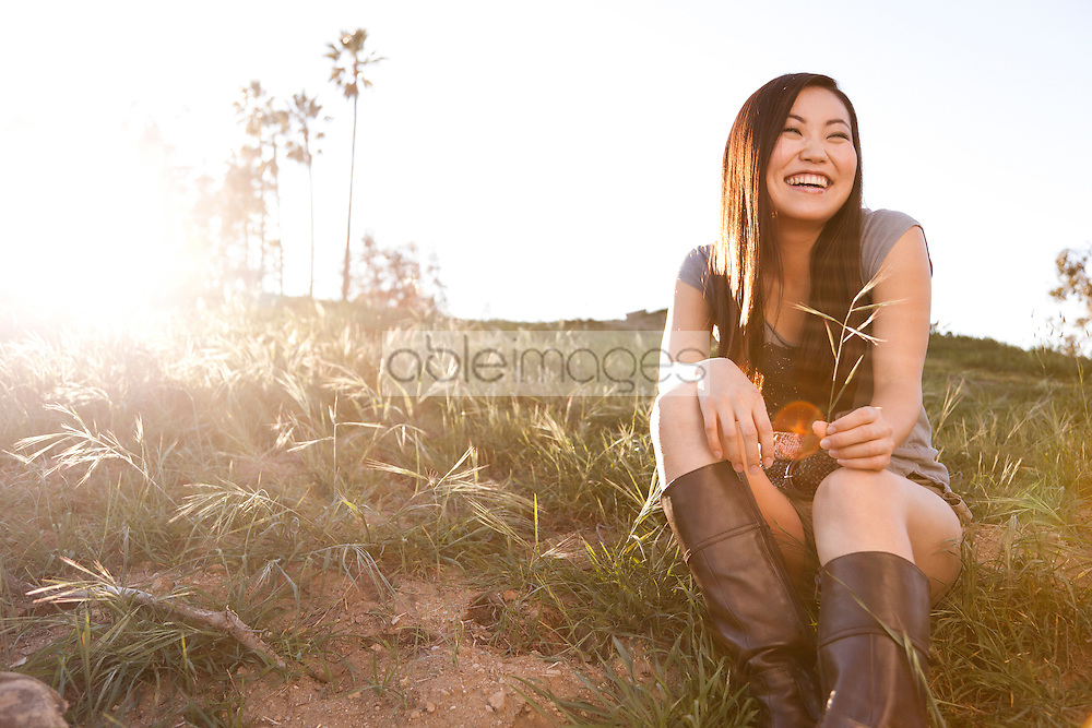 Smiling Young Woman Sitting on Field