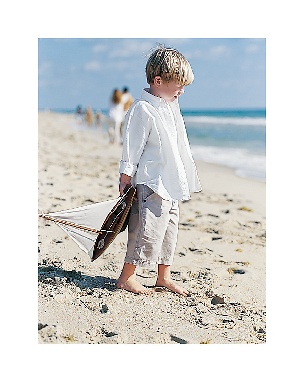 Photo of a young boy standing at the beach with a toy sailboat in his hand.