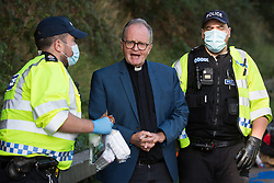 An Insulate Britain climate activist is arrested by Surrey Police after blocking the clockwise carriageway of the M25 between Junctions 9 and 10 as part of a campaign intended to push the UK government to make significant legislative change to start lowering emissions on 21st September 2021 in Ockham, United Kingdom. Both carriageways were briefly blocked before being cleared by Surrey Police. The activists are demanding that the government immediately promises both to fully fund and ensure the insulation of all social housing in Britain by 2025 and to produce within four months a legally binding national plan to fully fund and ensure the full low-energy and low-carbon whole-house retrofit, with no externalised costs, of all homes in Britain by 2030.
