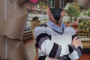 A detail of a torn shop poster showing a supermarket manager, in the window of a business in Orpington High Street, on 5th February 2020, in London, England. A near-perfect V has been ripped across the man's head to create a confusing and ambiguous graphic perspective.