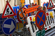 A stack of bi-lingual Belgian roadsigns are ready for use in roadworks on a pavement in Saint-Gilles Brussels