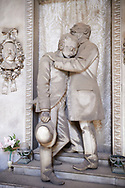 Picture and image of the stone sculpture of a grieving father and son standing at the doors of a tomb. Piccollo Tomb sculpted by G Moreno 1891. Section A, no 26, The monumental tombs of the Staglieno Monumental Cemetery, Genoa, Italy .<br /> <br /> Visit our ITALY PHOTO COLLECTION for more   photos of Italy to download or buy as prints https://funkystock.photoshelter.com/gallery-collection/2b-Pictures-Images-of-Italy-Photos-of-Italian-Historic-Landmark-Sites/C0000qxA2zGFjd_k<br /> If you prefer to buy from our ALAMY PHOTO LIBRARY  Collection visit : https://www.alamy.com/portfolio/paul-williams-funkystock/camposanto-di-staglieno-cemetery-genoa.html