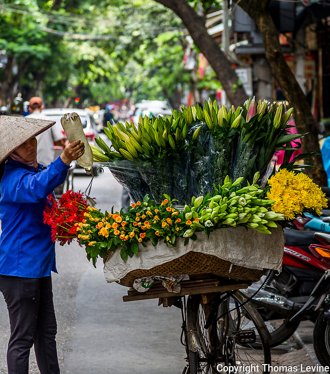 Vietnamese lady selling flowers from her bicycle in the Old Quarter of Hanoi. RAW to Jpg