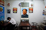 Forty years after his death, Mao Tsé-Tung is still framed and hung on walls around China. Pictures in large and gold-colored frames or simple printed in big sheets of paper are visible in restaurants, groceries or souvenirs shops, hidden alleys, homes and living rooms. Mao's face appears between pictures of traditional Chinese dishes, lists of food prices, wall fans, mirrors or other photographs - Mao Tse Tung.<br /> May 2016 - China.