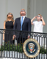 United States President Donald J. Trump, center, accompanied by first lady Melania Trump, left, and Barron Trump, right, look at the partial eclipse of the sun from the Blue Room Balcony of the White House in Washington, DC on Monday, August 21, 2017.<br /> (Photo by Ron Sachs/CNP/Sipa USA)