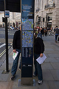 Two visitors to London read a street direction map in the capital's Regent Street. Both looking at the map on the reverse side to us and both holding A4 sheets of paper that possibly contains a printed map and an itinerary for their stay in the capital. They also wear matching tops and jeans and with legs in similar stances. In the background we see the curve of lower Regent's Street with shops and public buildings. The upright map is credited to Transport for London (TFL).