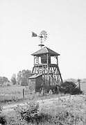 """2609 Windmill on the L. W. Brock farm, Sauvie Island, Route 13, Portland, Oregon. August 19, 1936. Windmill painted: """"Mitchell, Lewis & Staver, Portland"""" They were a very large distributor of agricultural implements and machinery."""