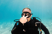 Underwater Hand signs scuba diver demonstrates the sign language for divers. Look: Point with two fingers to the eyes